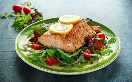 Baked salmon steak with tomato, onion, mix of green leaves salad in a plate. healthy food Imagens