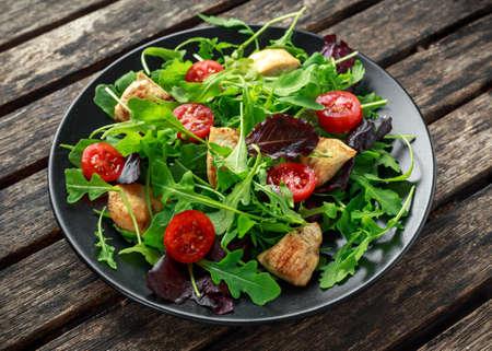 닭 가슴살, arugula, 견과류와 토마토 나무 테이블에 검은 접시에 신선한 샐러드.
