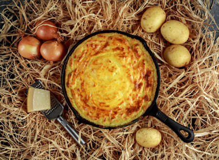 Mashed potato pie baked in rustic pan with onions and parmesan cheese on straw Stock Photo - 87806592
