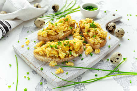 Homemade Quail Scrambled eggs on crispy toast, bread with green onion, chives on white board.