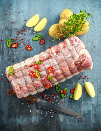 Raw Pork Loin cut ready to cook with chillies, potatoes and thyme Stock Photo