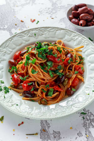 Vegetarian Italian Pasta Alla Puttanesca with garlic, olives, capers with on white plate. Zdjęcie Seryjne