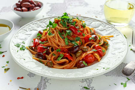 Vegetarian Italian Pasta Alla Puttanesca with garlic, olives, capers with on white plate.