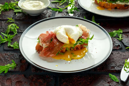 Bruschetta with cream cheese, wilde rucola, parma ham and poached egg served on white plate.
