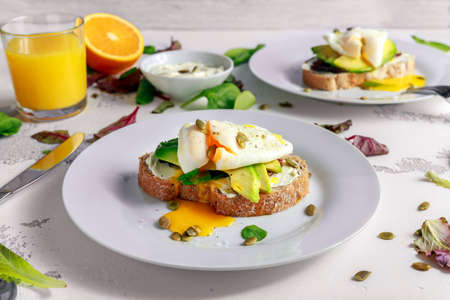 Sandwich, toast with avocado, soft cheese and poached egg on white background