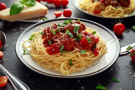 Spaghetti pasta gehaktballetjes met tomatensaus, basilicum, kruiden Parmezaanse kaas op donkere achtergrond Stockfoto