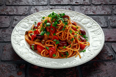 Vegetarian Italian Pasta Alla Puttanesca with garlic, olives, capers with on white plate. Stock Photo