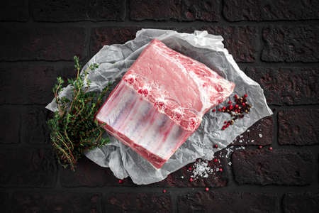 Traditional british raw pork loin joint bone-in with sea salt flakes, pepper and thyme