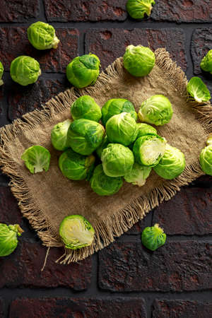 fresh raw brussels sprouts on a old stone rustic table Stock Photo