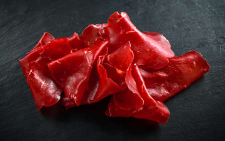 italian air-dried salted bresaola beef thinly sliced and served on stone board. Perfect appetizer Фото со стока