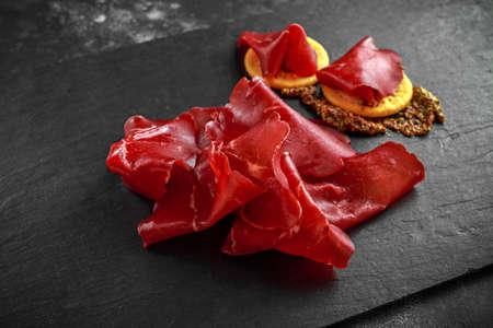 carne de bresaola salada al aire italiano salada finamente en rodajas y se sirve en el tablero de piedra. Aperitivo perfecto