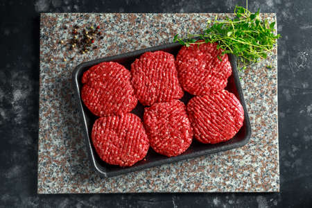 Handmade raw butchers steak burgers on marble chopping board