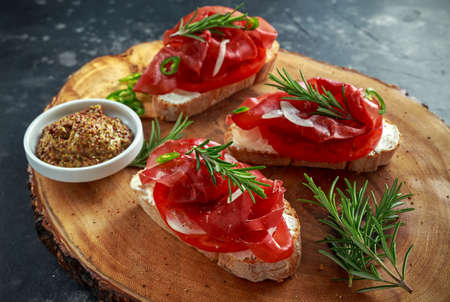 salted bresaola beef, Italian bruschetta with soft chees, onions, whole grain mustard, chillies and fresh rosmary. Stock Photo