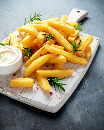 Homemade Baked Potato Fries with Mayonnaise and rosemary on white wooden board