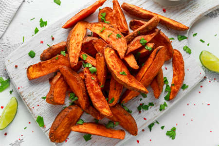 Healthy Homemade Baked Orange Sweet Potato wedges with fresh cream dip sauce, herbs, salt and pepper. Archivio Fotografico