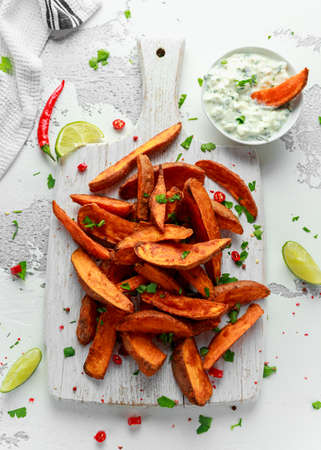 Healthy Homemade Baked Orange Sweet Potato wedges with fresh cream dip sauce, herbs, salt and pepper. Banco de Imagens
