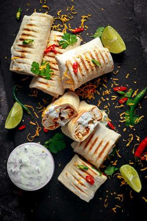 Gesunde gegrillte Hühner- und Petersilienverpackungen, geladen mit Käse, gedient mit den tiefen, Paprika- und Kalkscheiben des griechischen Joghurts