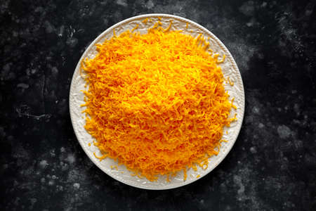 Grated red leicester cheese on plate view from above