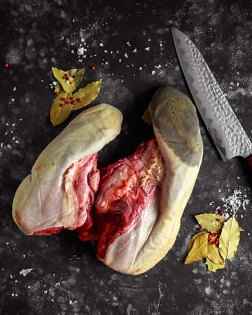 Raw ox calf tongues with bay leaves and red pepper corns, sea salt flakes and chopping knife Stok Fotoğraf - 92948106