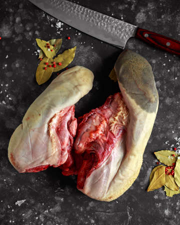 Raw ox calf tongues with bay leaves and red pepper corns, sea salt flakes and chopping knife