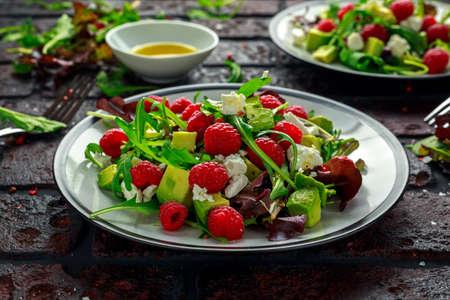 Verse smakelijke frambozen salade met avocado, groene groenten, noten, fetakaas, olijfolie en kruiden. gezond eten.