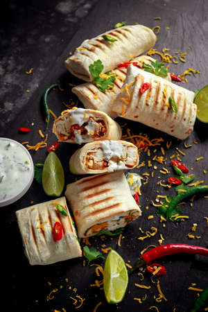 Healthy grilled chicken and parsley wraps, loaded with cheese, served with greek yogurt deep, chillies and lime slices