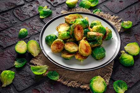 Homemade Roasted Brussel Sprouts with Salt, Pepper on a old stone rustic table. Foto de archivo