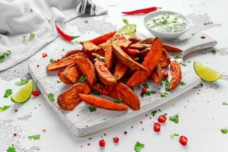 Healthy Homemade Baked Orange Sweet Potato wedges with fresh cream dip sauce, herbs, salt and pepper. Reklamní fotografie