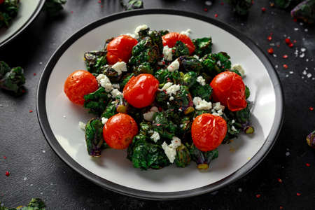 Homemade Roasted Green Kalettes salad with cherry tomatoes and feta cheese. healthy food Stock Photo