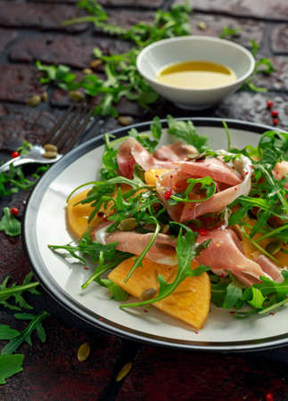 Fresh Tasty Persimmon salad with arugula, parma ham, olive oil, pumpkin seeds and herbs. autumn, winter healthy food Stock Photo