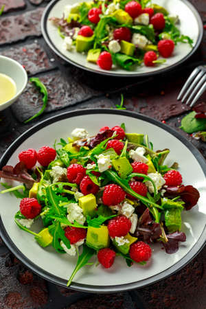 Fresh Tasty Raspberry salad with avocado, green vegetables, nuts, feta cheese, olive oil and herbs. healthy food.