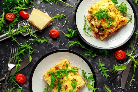 Zelfgemaakte lasagne met gehakt bolognese en bechamelsaus gegarneerd met wilde rucola, parmezaanse kaas Stockfoto