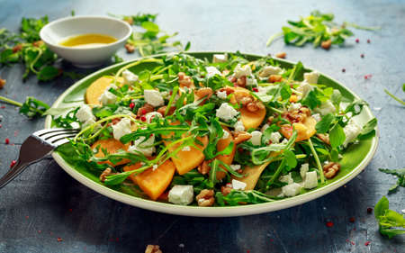 Fresh Tasty Persimmon salad with arugula, nuts, feta cheese, olive oil and herbs. healthy food