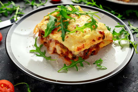 Homemade lasagna with minced beef bolognese and bechamel sauce topped wild arugula, parmesan cheese.