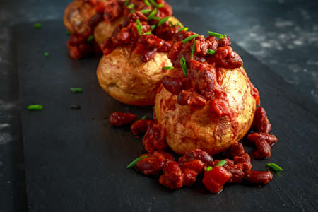 Baked jacket potatoes topped with red kedney beans in tomato sauce and chives served on stone board