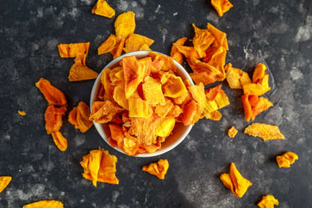 Tasty organic dried mango chips in bowl. healthy food Stock Photo