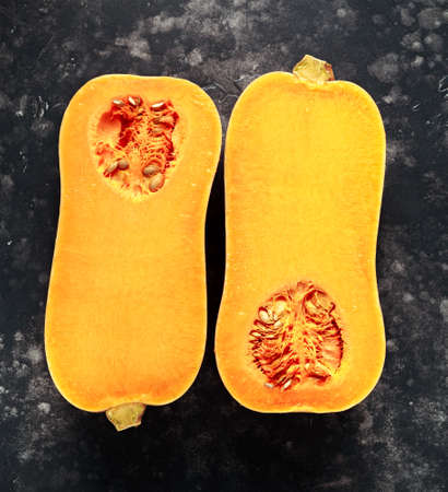 Halved butternut squash in a black background, vintage