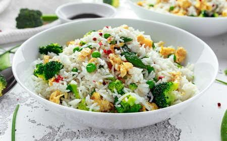 Fried rice with vegetables, broccoli, peas and eggs in a white bowl. healthy food Stockfoto