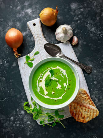Green sweet pea and mint soup with cream and olive oil drizzle served with grilled ciabatta toasts.