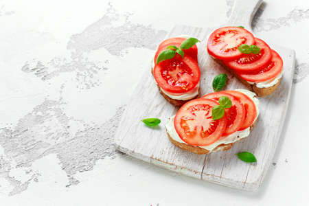 Bruschetta, toast with soft cheese, basil and tomatoes on a white wooden board. Italian healthy snack, food