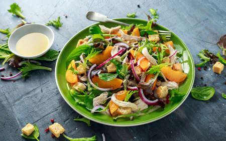 鶏胸肉、桃、赤玉ねぎ、クルトン、野菜をグリーンプレートに入れた新鮮なサラダ。健康食品