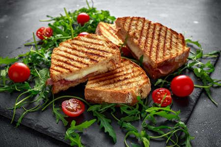 Gegrild spek, broodje kaas en geserveerd op stenen bord met rucola en tomaten Stockfoto