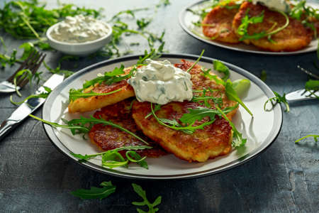Potato pancakes, draniki, hash browns or fritters served with... fresh wild rocket leaves salad.