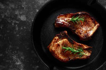 O lombo de carne de porco cozinhado desbasta na frigideira rústica, bandeja com alecrins. vista do topo. fundo Foto de archivo - 94461588