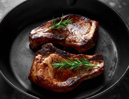 Cooked Pork Loin chops in rustic skillet, pan with rosemary.