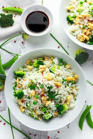 Fried rice with vegetables, broccoli, peas and eggs in a white bowl. soy sauce. healthy food