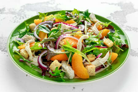 Fresh salad with chicken breast, peach, red onion, croutons and vegetables in a green plate. healthy food Zdjęcie Seryjne