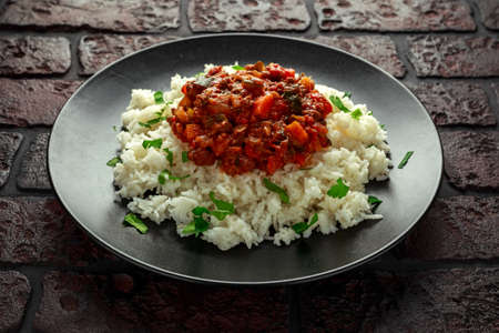Homemade beef mince and vegetable casserole served with rice on black plate.