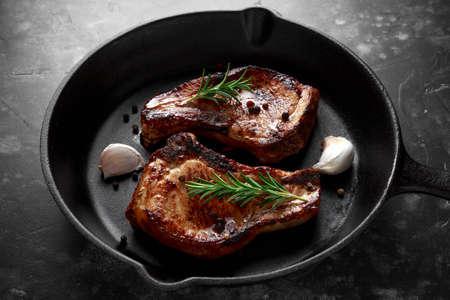 소박한 프라이팬에 로즈마리와 냄비 요리 돼지 고기 허리 볶음. 평면도. 배경