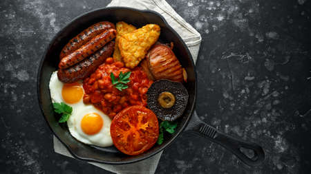 Full English breakfast with bacon, sausage, fried egg, baked beans, hash browns and mushrooms in rustic skillet, pan. Фото со стока